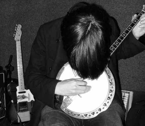一张Jonny演奏班卓琴的照片,他的no2 tele就潜伏在左侧。